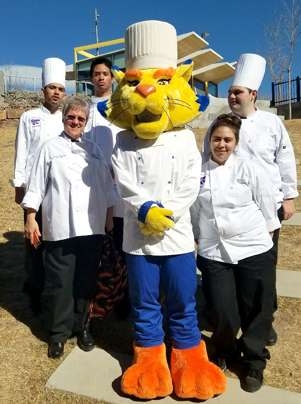 Image of CHS Culinary students and their teacher posing with mascot